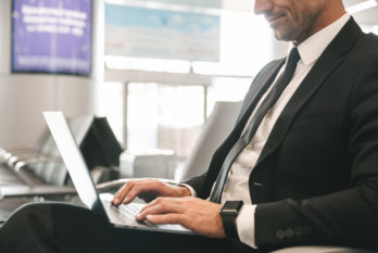 Cropped image of businessman dressed in suit using laptop computer while sitting at the airport lobby